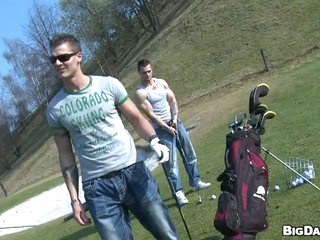 Husky inviting studs joshing each other in the golf course